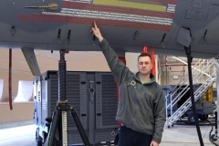 U.S. Air Force Tech. Sgt. Jendrysik, 104th Maintenance Group, aircraft structural maintenance technician, points out his name on the new graphic on the wing's flagship F-15C Eagle in the wing's Main Hangar Jan. 22, 2021. The graphic featured on both sides of the F-15, appears to display the American Flag, but upon closer look, the hundreds of names of members in the 104th Fighter Wing are visible. (U.S. Air National Guard photo by Staff Sgt. Hanna Smith)