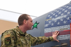 U.S. Air Force Master Sgt. Leo Burbee, 104th Maintenance Group, aircraft structural maintenance supervisor, touches the graphic on the wing's flagship F-15C Eagle at Barnes Air National Guard Base, Mass. Jan. 22, 2021. The graphic featured on both sides of the F-15, appears to display the American Flag, but upon closer look, the hundreds of names of members in the 104th Fighter Wing are visible. (U.S. Air National Guard photo by Staff Sgt. Hanna Smith)